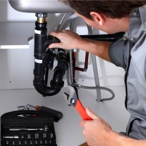 plumber fixing leaking pipe